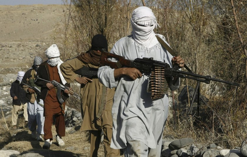 Taliban fighters pose with weapons