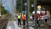 A Swiss police officer stands near workers cleaning a platform after a 27-year-old Swiss man's attack on a Swiss train at the railway station in the town of Salez, Switzerland August 13, 2016.