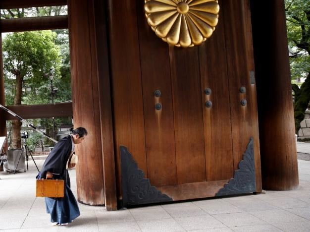 A man bows his head as he enters Yasukuni Shrine on the anniversary of Japan's surrender in World War Two in Tokyo, Japan, August 15, 2016.