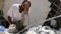 A man waits as Syrian civil defence workers look for survivors under the rubble of a collapsed building following reported air strikes on July 17, 2016 in Aleppo