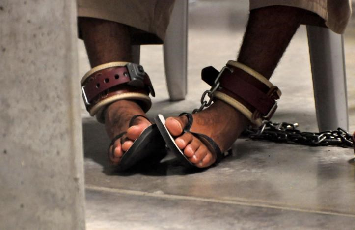 In this photo, reviewed by a U.S. Department of Defense official, a Guantanamo detainee's feet are shackled to the floor as he attends a 'Life Skills' class inside the Camp 6 high-security detention facility at Guantanamo Bay U.S. Naval Base April 27, 2010.