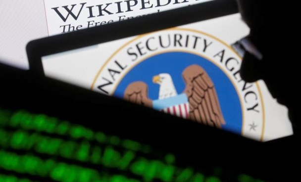 A man is seen near cyber code and the U.S. National Security Agency logo in this photo illustration taken in Sarajevo March 11, 2015.