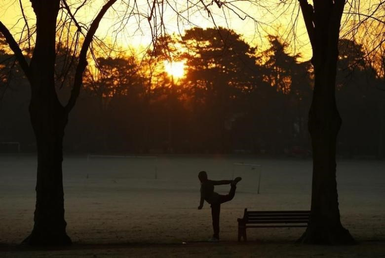 A woman exercises as the sun rises over Victoria Park in Leicester, central England, December 30, 2014.