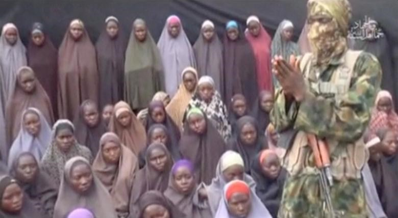 A still image from a video posted by Nigerian Islamist militant group Boko Haram on social media, seen by Reuters on August 14, 2016, shows a masked man talking to dozens of girls the group said are school girls kidnapped in the town of Chibok in 2014. Social Media