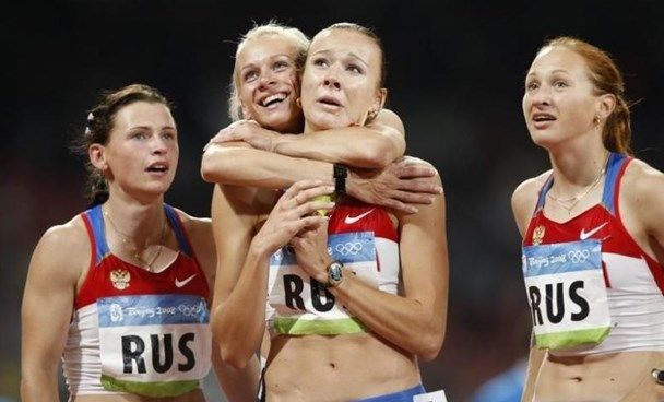 (From L to R) Evgeniya Polyakova of Russia and her teammates Yulia Gushchina, Yuliya Chermoshanskaya and Aleksandra Fedoriva look at the scoreboard after the women's 4 x 100m relay final of the athletics competition in the National Stadium at the Beijing 2008 Olympic Games August 22, 2008. The Russian team finished first.