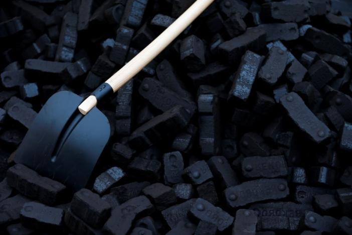A shovel is placed over coal briquettes during a protest in front of the chancellery in Berlin December 3, 2014.