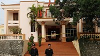 Police officers stand guard in front of the office building of the Party's committee of Yen Bai Province, where two provincial leaders were shot to death on Aug. 18