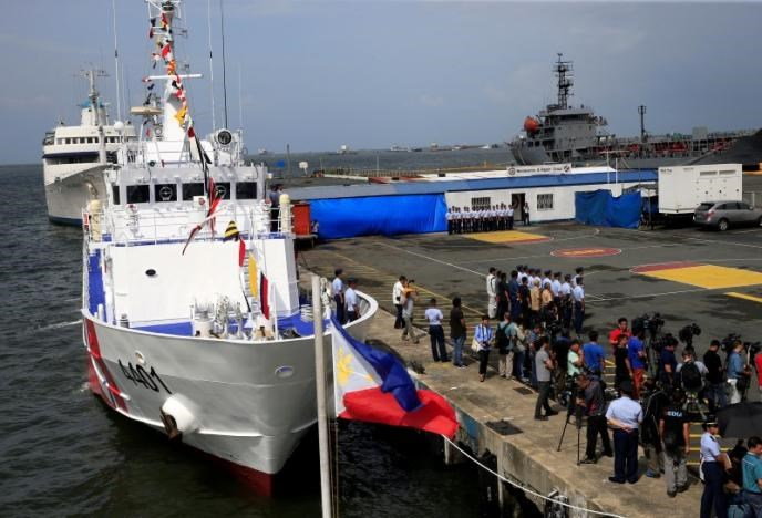 A Philippine flag flutters in front of the BRB Tubbataha, a coast guard ship, one of 10 multi-role vessel the Philippines is acquiring from Japan under a 8.8 billion pesos (US$ 190million) agreement, as it arrives in south harbor, metro Manila, Philippines August 18, 2016.