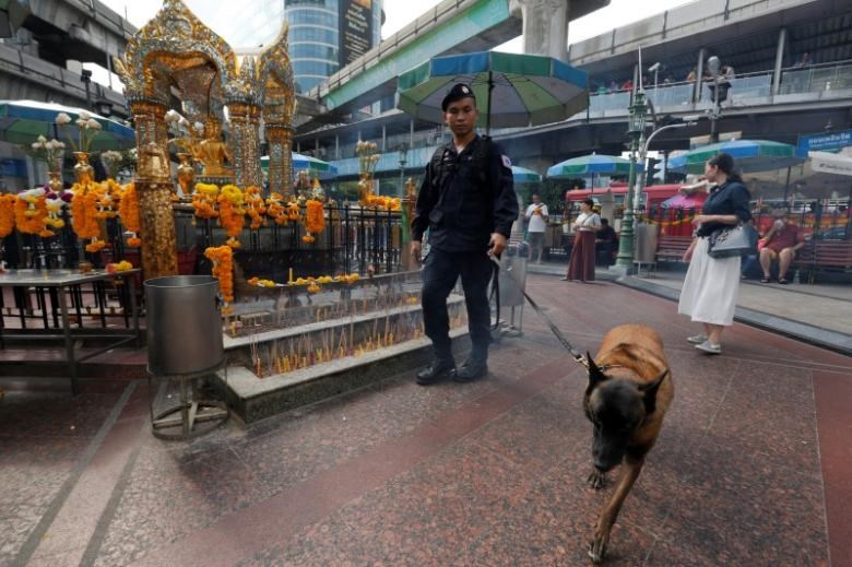 A Thai policeman and his dog inspect around the Erawan shrine during the first anniversary of the bombing of the shrine, in central Bangkok, Thailand, August 17, 2016.
