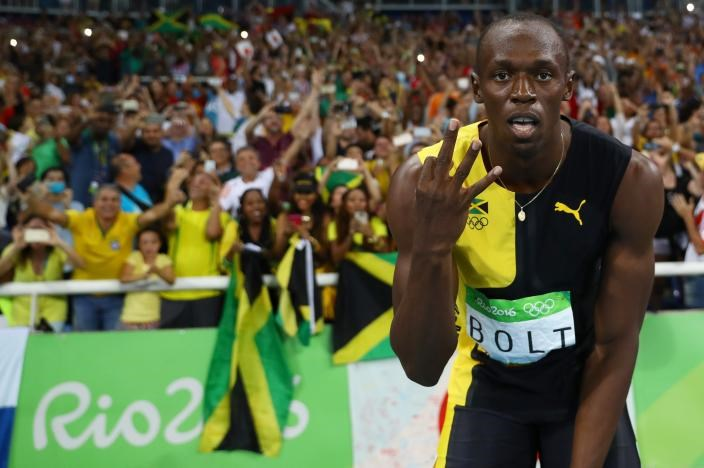 Usain Bolt (JAM) of Jamaica celebrates winning the Jamaican team's gold medal.
