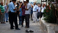 A police officer secures the scene of an explosion as locals stand next to him after a suspected suicide bomber targeted a wedding celebration in the Turkish city of Gaziantep, Turkey, August 21, 2016.