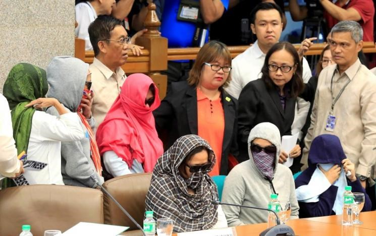 Relatives of slain people cover their faces as they attend a Senate hearing investigating drug-related killings at the Senate headquarters in Pasay city, metro Manila, Philippines August 22, 2016.