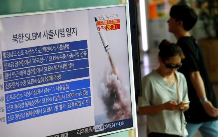Passengers walk past a TV screen broadcasting a news report on North Korea's submarine-launched ballistic missile fired from North Korea's east coast port of Sinpo, at a railway station in Seoul, South Korea, August 24, 2016