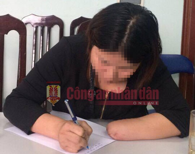 Ly Thi N. writes a statement at an investigator's office in Hanoi. Photo credit: CAND