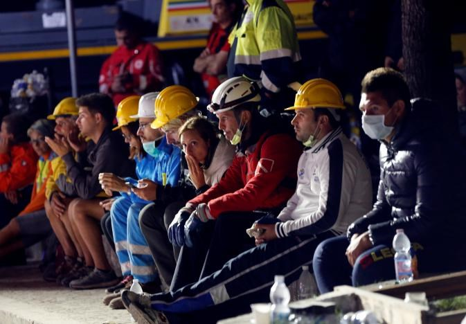 Rescue workers take a rest following an earthquake in Amatrice, central Italy, August 24, 2016.