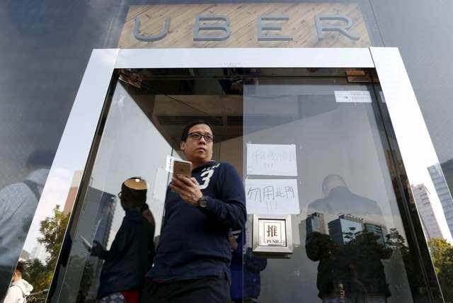 A driver leaves the office of taxi-hailing service Uber Inc during a driver recruitment event in Hong Kong, China December 29, 2015.