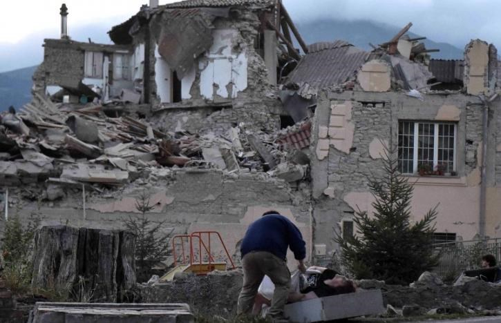 A man helps a woman in front of a collapsed building following an earthquake in Amatrice, central Italy, August 24, 2016