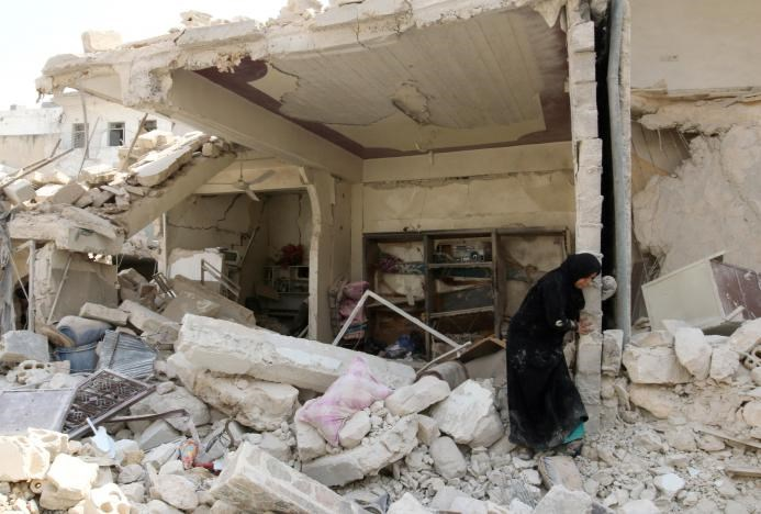 A woman inspects the damage after an airstrike in the rebel held Bab al-Nairab neighborhood of Aleppo, Syria, August 25, 2016.