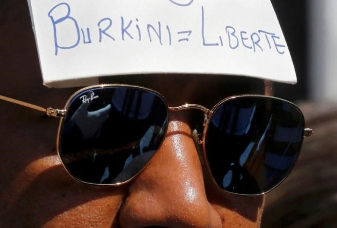 A man wears a placard with the message, 'Burkini = Liberty' outside the Conseil d'Etat after France's highest administrative court suspended a ban on full-body burkini swimsuits that has outraged Muslims and opened divisions within the government, pending a definitive ruling, in Paris, France, August 26, 2016.