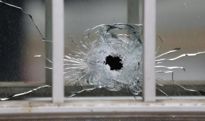 A bullet's impact is seen on a window at the scene after a shooting at the Paris offices of Charlie Hebdo, a satirical newspaper, January 7, 2015.