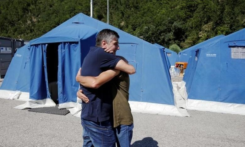 Two survivors hug at a tent camp set up as temporary shelter following an earthquake in Pescara del Tronto, central Italy, August 26, 2016.