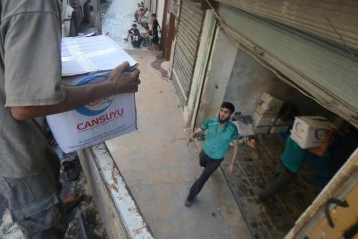 Workers unload food aid parcels that were brought into rebel held areas of Aleppo through civil defence vehicles from a newly opened corridor that linked besieged opposition held eastern Aleppo with western Syria that was captured recently by rebels, in Aleppo August 12, 2016.