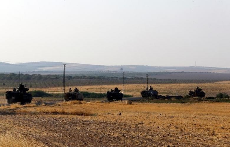 Turkish armoured personnel carriers drive towards the border in Karkamis on the Turkish-Syrian border in the southeastern Gaziantep province, Turkey, August 27, 2016.