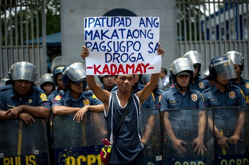 An activist hold a banner in front of the Philippine National Police headquarters during a protest condemning extra-judicial killings in President Rodrigo Duterte's campaign against drugs, in Manila on August 24, 2016