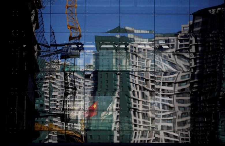 A construction site and a residential building are reflected on the glass wall of a building in Beijing, December 15, 2014.