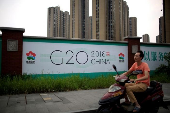 A man rides an electronic bike past a billboard for the upcoming G20 summit in Hangzhou, Zhejiang province, China, July 29, 2016. Picture taken July 29, 2016.