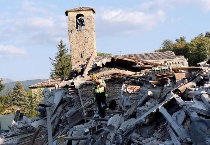 A rescue worker and a dog search among debris following an earthquake in Amatrice, central Italy, August 27, 2016.
