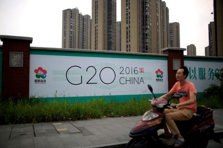 A man rides an electronic bike past a billboard for the upcoming G20 summit in Hangzhou, Zhejiang province, China, July 29, 2016.