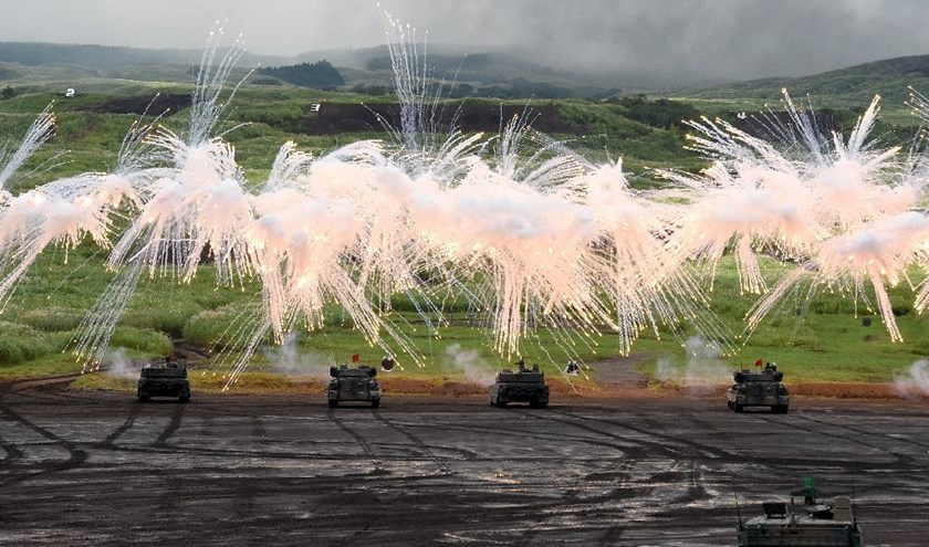 Japanese Ground Self-Defense Force tanks move amongst an umbrella of barrage during an annual live fire exercise, at the Higashi-Fuji firing range in Gotemba, Shizuoka prefecture, on August 25, 2016