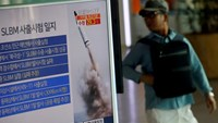 A passenger walks past a TV screen broadcasting a news report on North Korea's submarine-launched ballistic missile fired from North Korea's east coast port of Sinpo, at a railway station in Seoul, South Korea, August 24, 2016