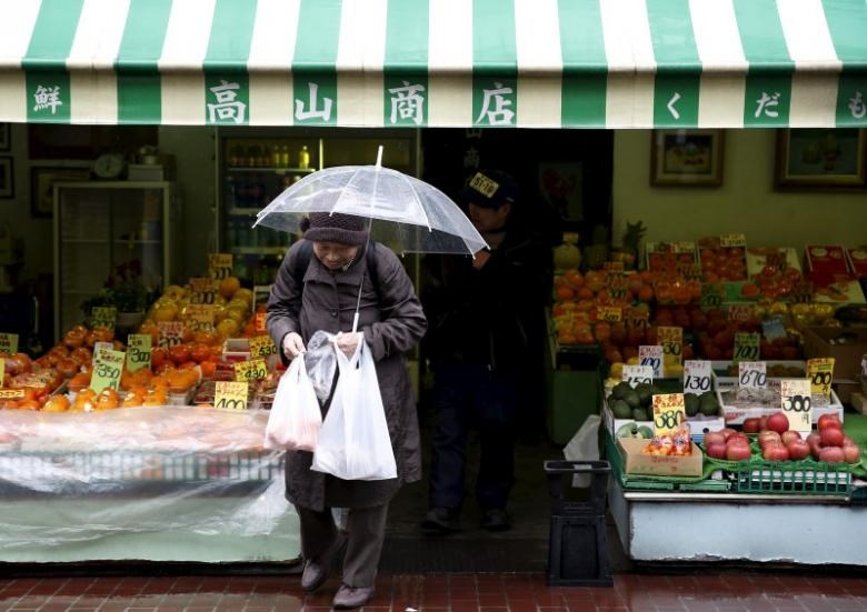 A shopper holding plastic bags walks out from a greengrocer's at Tokyo's Sugamo district, an area popular with the Japanese elderly, in Tokyo, Japan, March 14, 2016.
