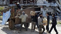 Men unload boxes of U.N. humanitarian aid at a besieged area of Homs February 12, 2014.