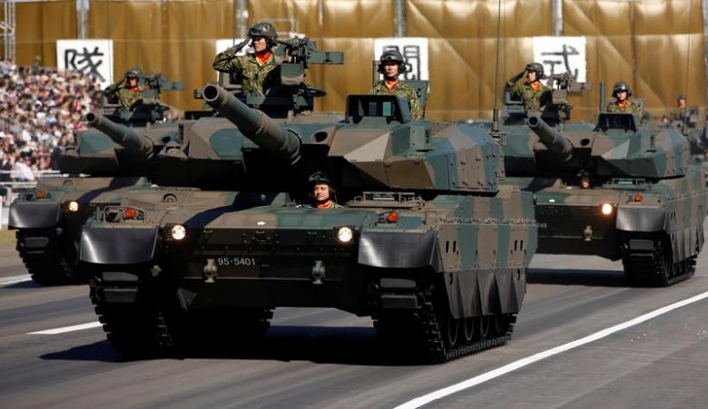 Members of a tank unit of Japan's Self-Defense Forces (SDF) riding on Type-10 armoured tanks take part in a military review during the annual troop review ceremony at Asaka Base in Asaka, near Tokyo October 27, 2013.