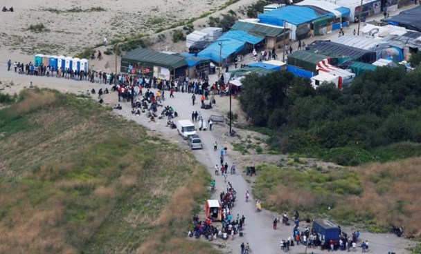Migrants queue near makeshifts shops in what is known as the ''Jungle'', a sprawling camp in Calais, France, August 14, 2016.