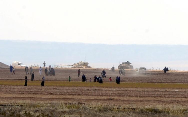 Syrian civilians, with Turkish Army tanks in the background, walk through the Turkish border as they are pictured from a village in Kilis province, Turkey, September 3, 2016.