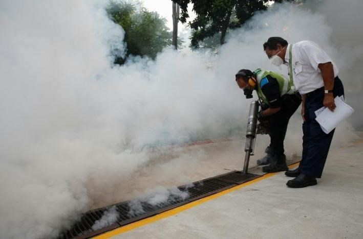 A worker fogs the drains in the common areas of a public housing estate at an area where locally transmitted Zika cases were discovered in Singapore August 31, 2016.
