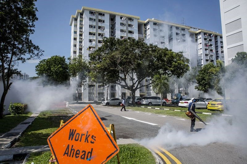Pest control workers fumigate the grounds of apartment block in Singapore on Sept. 3. Photographer: Ulet Ifansasti/Getty Images