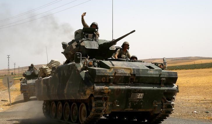 A Turkish soldier on an armoured personnel carrier waves as it is driven from the border back to their base in Karkamis on the Turkish-Syrian border in the southeastern Gaziantep province, Turkey, August 27, 2016.