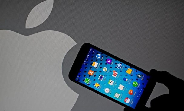 A Samsung Galaxy S5 smartphone is held next to a logo of Apple in this September 23, 2014 illustration photo in Sarajevo.