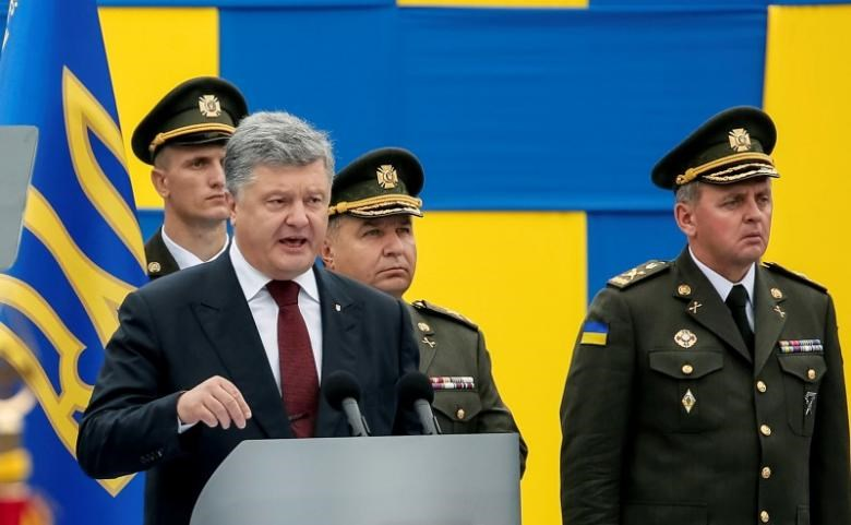 Ukrainian President Petro Poroshenko speaks as Defence Minister Stepan Poltorak (2nd R) and Chief of Staff of Ukraine's Armed Forces Viktor Muzhenko (R) look on during Ukraine's Independence Day military parade in central Kiev, Ukraine August 24, 2016.