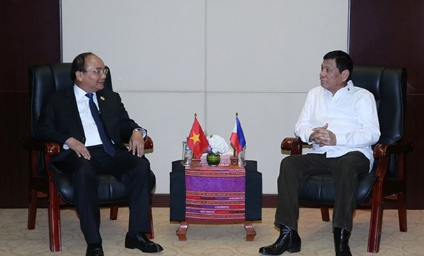 Prime Minister Nguyen Xuan Phuc (L) and Philippines' President Rodrigo Duterte meet on the sidelines of the ASEAN summit in Laos