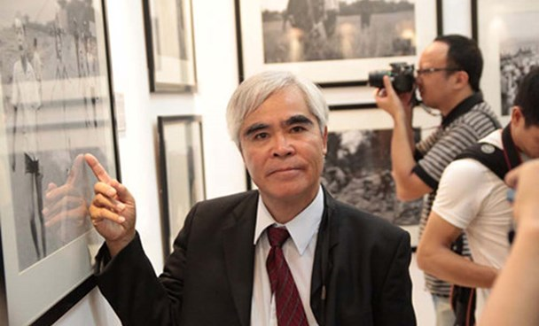 """Photographer Nick Ut stands beside his iconic Vietnam War picture of the """"Napalm Girl"""" at an event in Hanoi in June 2015"""