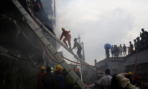 Firefighters extinguish a fire at a food and cigarette packaging factory outside of Dhaka, Bangladesh, September 10, 2016.