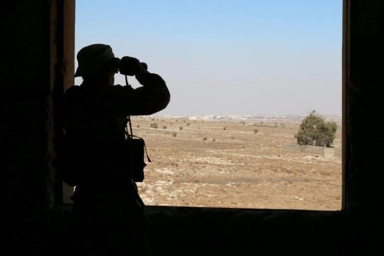 A rebel fighter looks through binoculars in Quneitra countryside, Syria September 10, 2016.