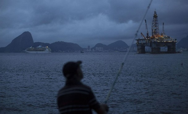 In this April 21, 2015 file photo, a man fishes in Guanabara Bay where an oil platform floats, backdropped by Sugar Loaf Mountain, left, in Niteroi, Brazil.