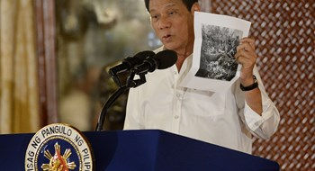 President Rodrigo Duterte holds up a photo, citing accounts of US troops who have killed Muslims during the US occupation of the Philippines in the early-1900s during a speech at the oath-taking of newly appointed government officials, at Malacanang palace in Manila on Sept. 12.